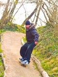 Kerel op zijn skateboard dat onderaan een weg vliegt Stock Fotografie