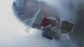 Kerel schoonmakende die voorruit van binnenuit de auto wordt geschoten stock video