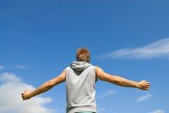 Kerel in sporten die zich op blauwe hemelachtergrond kleden Royalty-vrije Stock Foto's