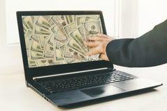 Kerel of zakenman het geld van de holdingsbok in zijn hand Laptop op de achtergrond royalty-vrije stock foto's