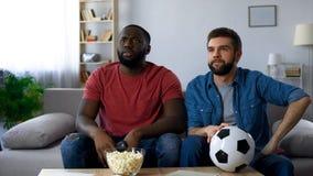 Kerels door nederlaag van favoriet team, het letten op voetbalwedstrijd op TV worden gefrustreerd die stock fotografie