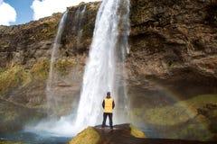 Kereltoerist die zich dichtbij waterval bevinden die, achtermening genieten van royalty-vrije stock foto's