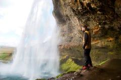 Kereltoerist die zich dichtbij waterval bevinden die van de mening genieten royalty-vrije stock afbeeldingen