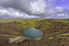 Kerid crater vista. Looking down into volcanic crater with red walls under dramatic storm clouds stock photo