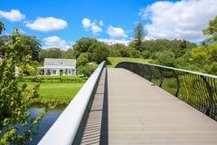 KERIKERI, NZ - 1月10,2015 :历史的使命驻地肯普议院看法从现代金属桥梁的 库存照片