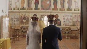 Kerk bij het huwelijk De bruid en de bruidegom in de kerk Intens gebed in de Kerk stock videobeelden