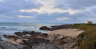 Kerk die het strand overzien onder de wolken stock fotografie