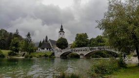 Kerk en brug op Bohinj-meer in Slovenië Zeer bewolkte dag stock fotografie