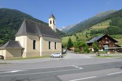 Kerk en traditioneel chalet in Heiligenblut op Oostenrijk royalty-vrije stock afbeelding