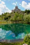 Kerk met bezinning in mooi turkoois meer   Stock Fotografie