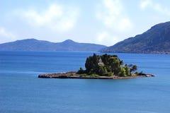 Kerk onder groene bomen op klein eiland in het midden van het Ionische overzees Berg en overzeese mening Royalty-vrije Stock Foto