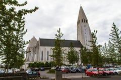 Kerk in Reykjavik, bomen en auto's zijaanzicht royalty-vrije stock afbeeldingen