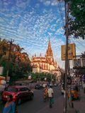 Kerk van lang schot op zonnige avonddag met blauwe hemel en bezige weg, mensen, platform, boom, auto, voertuigen Royalty-vrije Stock Afbeelding