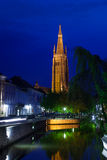 Kerk van Onze Dame Bruges bij nacht van kanaal Stock Foto