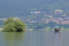 Kerkini lake view ,Greece. Tourists tour boat  in Kerkini lake and traditional village in the distance, Macedonia, Greece.Lake Kerkini  is an artificial Royalty Free Stock Image