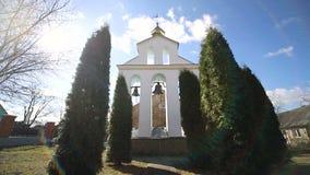 Kerkklokken op een zonnige dag in een sterke wind De wind schudt de bomen dichtbij de klokketoren en Sonechka glanst in stock footage