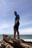Kerl auf einem Felsen auf dem Strand Stockfotografie
