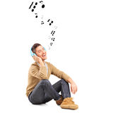 Kerl auf einer hörenden Musik des Bodens auf Kopfhörern und Anmerkungen um hallo Stockfotos