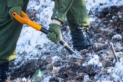 Kerl in den Militäruniformen gräbt die Erde im Winter Stockfotografie
