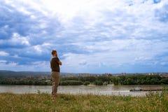 Kerl, der über Fluss auf der Stadt schaut Stockfoto