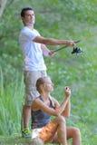 Kerl, der Angelruten- und Freundinsignalement hält Lizenzfreie Stockfotografie