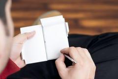 Kerl, der Anmerkungen auf einem kleinen Tagebuch beim Sitzen entspannt in einem hölzernen ausgebreiteten Raum macht Stockfotos