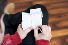 Kerl, der Anmerkungen auf einem kleinen Tagebuch beim Sitzen entspannt in einem hölzernen ausgebreiteten Raum macht Lizenzfreies Stockbild