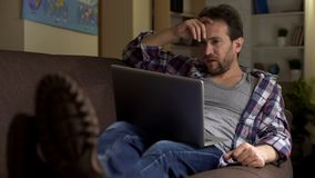 Kerl, der auf dem Sofa, den Laptop betrachtend sitzt, verärgert mit empfangenen Nachrichten, Bitterkeit lizenzfreie stockbilder