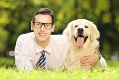 Kerl, der auf einem Gras liegt und seinen Hund in einem Park umarmt Stockbild