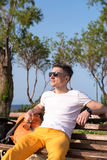 Kerl, der auf einer Bank nahe dem Meer sitzt Stockbilder
