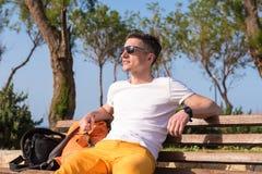 Kerl, der auf einer Bank nahe dem Meer sitzt Stockfotos