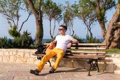 Kerl, der auf einer Bank nahe dem Meer sitzt Stockfotografie