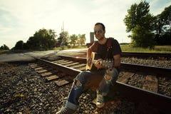 Kerl, der auf Schienen mit Gitarre sitzt Lizenzfreie Stockbilder