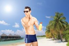 Kerl, der auf Sonnencreme, auf einem Strand mit Palmen und Häuschen an sich setzt Stockbild