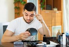 Kerl, der Augenbrauenhaar entfernt Stockfotografie