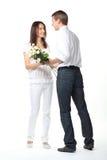 Kerl, der Blumen junger Dame darstellt Stockbilder