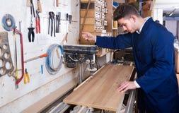 Kerl, der Bohrmaschine an der Werkstatt verwendet Lizenzfreie Stockbilder