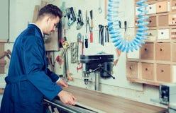 Kerl, der Bohrmaschine an der Werkstatt verwendet Stockfotografie