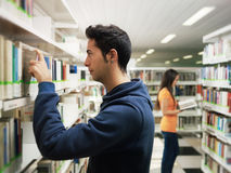 Kerl, der Buch vom Regal in der Bibliothek nimmt Stockfotos