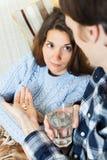 Kerl, der der unwohlen Freundin Medikament gibt Stockbild