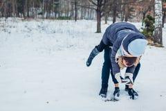Kerl, der draußen seiner Freundin Doppelpol in den liebevollen Paaren der Winterwaldjunge haben Spaß gibt lizenzfreie stockfotos