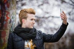 Kerl, der draußen Selbstphoto mit Telefon macht Stockbilder