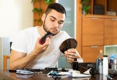 Kerl, der durch elektrischen Rasierapparat sich rasiert Lizenzfreie Stockfotos