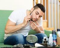 Kerl, der durch elektrischen Rasierapparat sich rasiert Lizenzfreie Stockfotografie