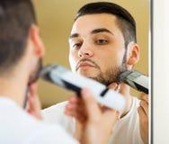 Kerl, der durch elektrischen Rasierapparat sich rasiert Stockbilder