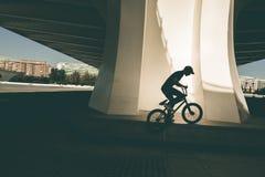 Kerl, der ein bmx Fahrrad auf die Straße reitet Freistil BMX in der Stadt stockfoto