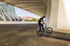 Kerl, der ein bmx Fahrrad auf die Straße reitet Freistil BMX in der Stadt stockfotografie