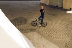Kerl, der ein bmx Fahrrad auf die Straße reitet Freistil BMX in der Stadt stockbilder