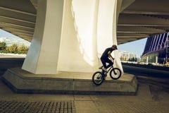 Kerl, der ein bmx Fahrrad auf die Straße reitet Freistil BMX in der Stadt lizenzfreie stockbilder