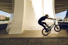 Kerl, der ein bmx Fahrrad auf die Straße reitet Freistil BMX in der Stadt lizenzfreie stockfotografie